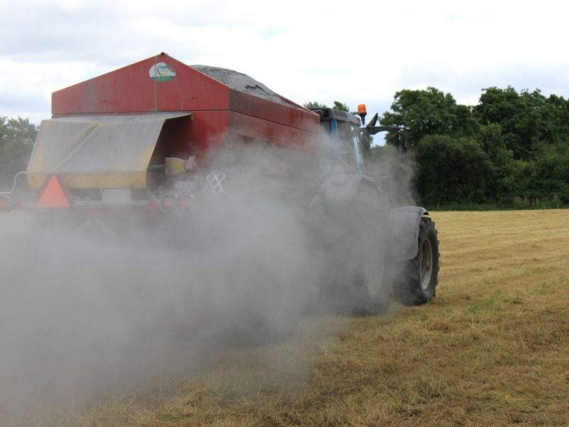 Tractor spreading agri lime in field